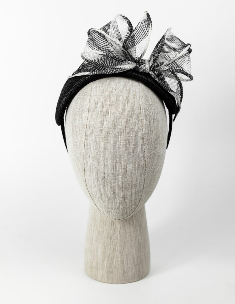 Black straw headpiece with black and white rolled sinamay bow